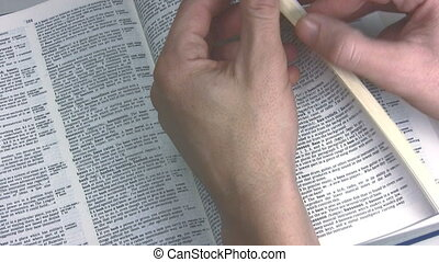 Copyright - Pair of hands browsing through a dictionary,...