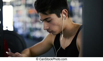 Hispanic man in gym resting, holding smart phone,listening...