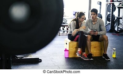 Fit couple in modern crossfit gym with smartphone. -...