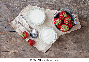 Yogurt with strawberries in a glass and a bucket with fresh...