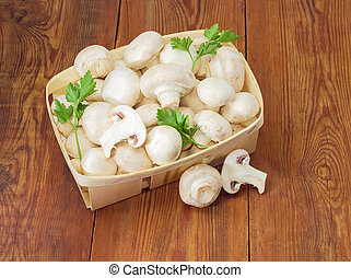 Cultivated button mushrooms in the wooden basket