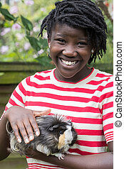 Portrait Of Girl In Garden Looking After Pet Guinea Pig