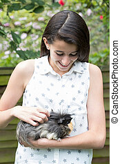 Girl In Garden Looking After Pet Guinea Pig