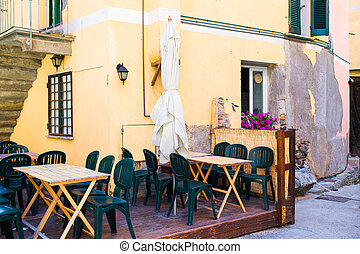 Empty openair cafe with colorful tables at italian old...