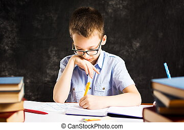 Boy writing in notebook on the desk covered in books