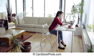 Woman at home working on laptop, making a phone call. -...