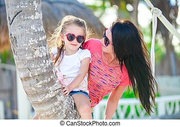 Happy mom and kid enjoying time together at the white beach on palm tree