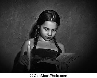 little girl reading book and studying in candle light in...