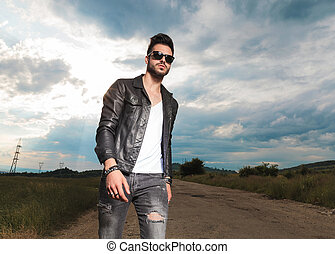 man in leather jacket walking on a country road