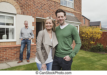 Happy Couple With New Home - Proud father watches as his son...