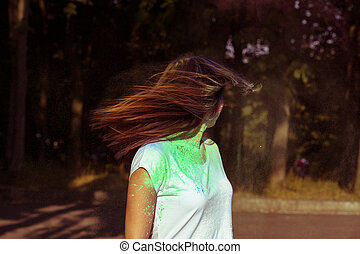 Beautiful young woman with long hair in motion covered with Gulal powder