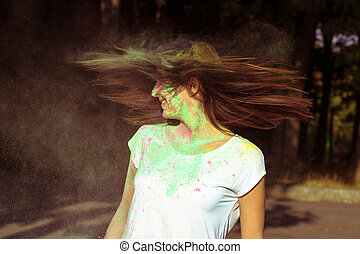 Young brunette woman with long hair in motion with colorful Gulal powder
