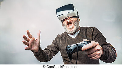 Mature man wearing virtual reality goggles / VR Glasses to...