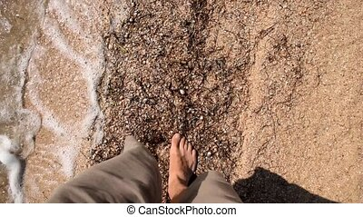 Feet of young man walking on beach - Point of view of young...