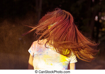 Brunette young woman with long hair in motion covered with dry Gulal powder