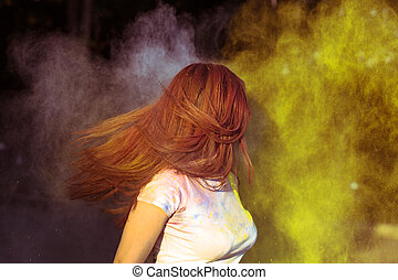 Young brunette woman with long hair in motion covered with colorful Gulal powder