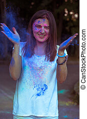 Lovely smiling model tossing up blue powder Gulal in the...