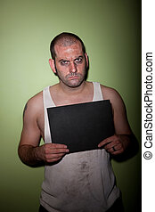 Angry man in mugshot - Man in wife beater takes mugshot with...