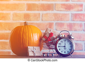 pumpkin and alarm clock with shopping cart full of gifts
