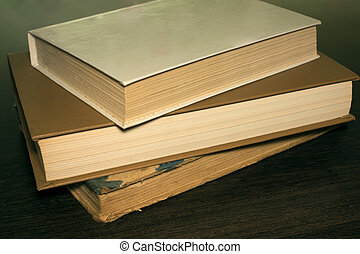 books on a wooden table new and old