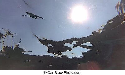 Underwater slow motion shot of a sun with small waves -...