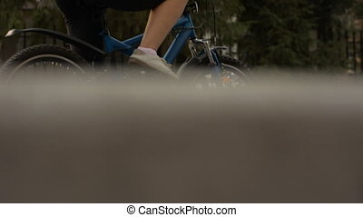 Woman on a bicycle standing on the road scratching her leg