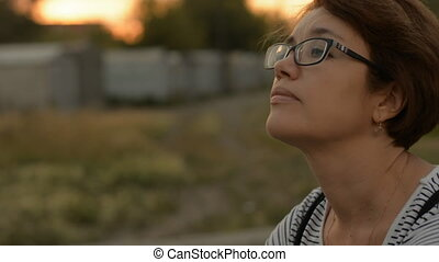 Close-up of a pensive woman with glasses on the background...