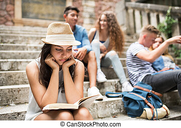 Teenage student girl sitting on stone steps reading a book....