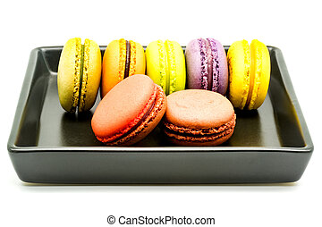 Row of macarons in a black plate