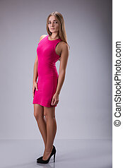 young lady wearing pink dress over grey background.