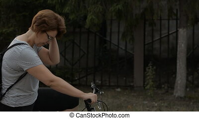 Woman in glasses on a bicycle outdoors rolling.