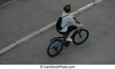 Woman in a striped blouse rides a bicycle on an asphalt...