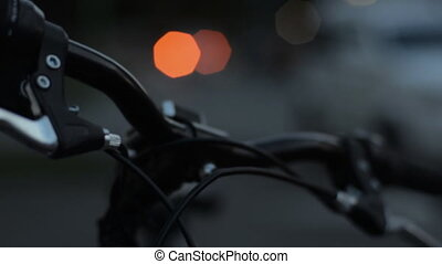 At night the steering wheel of a bicycle and a bokeh of...