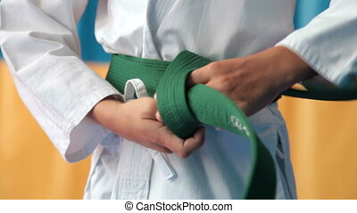 green belt - martial arts athlete tying the knot to his...