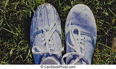 Female feet wears sneakers in blue jeans color sports shoes...