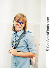 Outdoor portrait of a cute little 9-10 year old girl wearing...