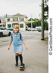 Funny little schoolgirl riding skateboard outside, back to school concept, film look toned image