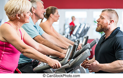 Personal trainer instructs senior woman about spinning at...