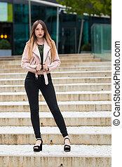 Portrait of informal fashionable girl on modern building...