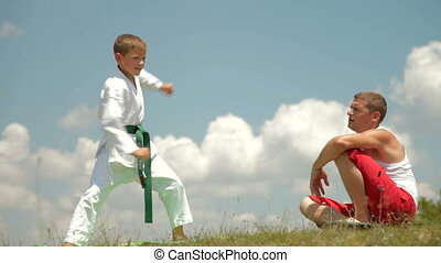 son and father practicing karate on the nature on a sunny...
