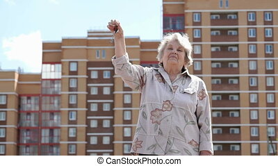 Smiling mature old woman raising hand up with keys