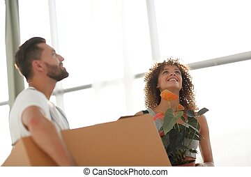 Husband and wife bring boxes with things to a new apartment....