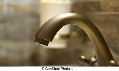 The dripping faucet. Drops fall from the old tap.
