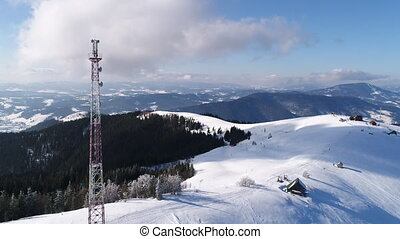 Flying over radio communications tower, mountain snow...