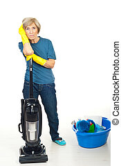 Tired cleaning senior woman rest with hand on vacuum cleaner...