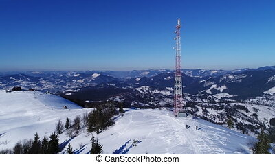 Flying over communications tower, mountain snow covered...