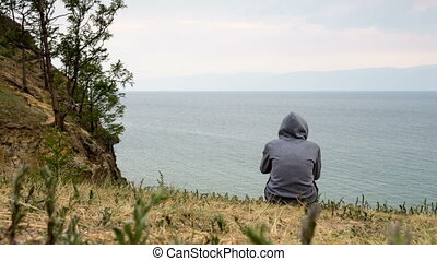 A man sits on the seashore in cloudy weather and...