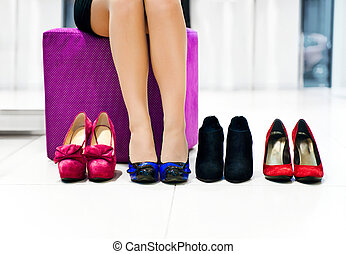 Woman chooses shoes - The woman in shop chooses shoes
