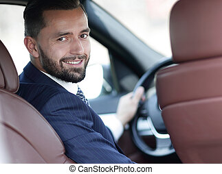 businessman sitting at the wheel of a car and looking at the...