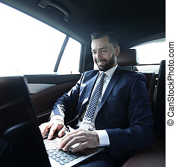 businessman sitting in the back-seat of a car, using his laptop